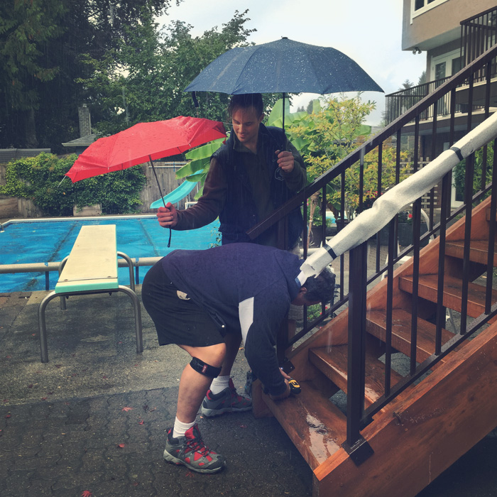 Adam's dad is installing a new railing in the rain - while Adam protects his most valuable assets